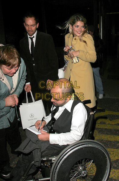 HOLLY WILLOUGHBY & GUEST.British Comedy Awards 2006, London Television Studios, London, UK. - Departures.December 13th, 2006.full length goody bag beige brown coat wheelchair the office signing autograph.CAP/AH.©Adam Houghton/Capital Pictures