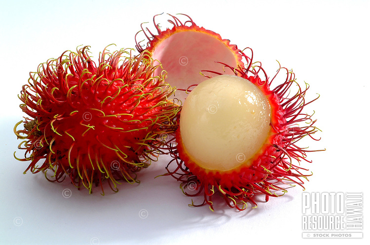 Studio photo of whole and sectioned rambutans on white background.