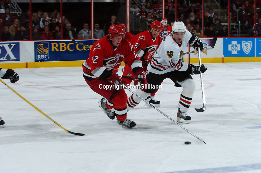 Carolina Hurricanes' Eric Staal (12) carries the puck up the ice defended by the Chicago Blackhawks' Patrick Sharp (10) Tuesday, Dec. 13, 2005 in Raleigh, NC. Carolina won 5-3.