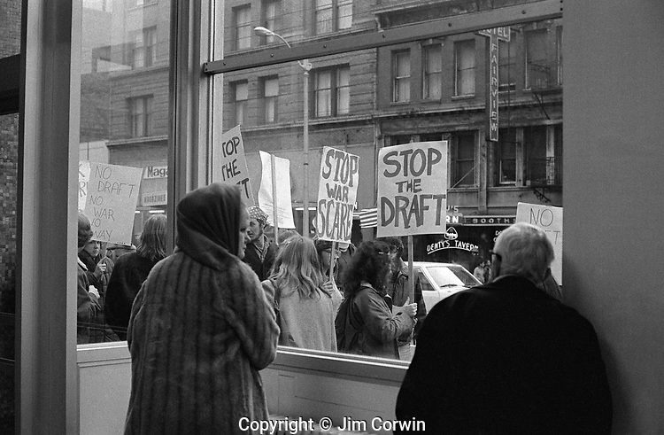 War protesters at downtown post office building in downtown Seattle with people in post office looking out window