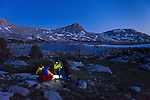 Backpackers play cards after sunset at L Lake in the High Sierra mountains over Pine Creek Pass west of Bishop, California, July 2016.