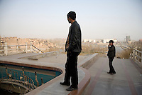 Uighur men look out over Kashgar, Xinjiang, China, from a small amusement park from which the Old City (left horizon) and new development (right horizon) across the Tuman River.