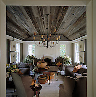 A wrought-iron candelabra hangs from the wooden ceiling of the living room which is furnished with taupe sofas and wing-backed armchairs