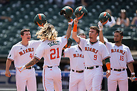 Hunter Tackett (21) of the Miami Hurricanes is greeted at home plate by teammates Michael Burns (44), Carl Chester (9), and Edgar Michelangeli (16) after hitting a grand slam against the Georgia Tech Yellow Jackets during Game One of the 2017 ACC Baseball Championship at Louisville Slugger Field on May 23, 2017 in Louisville, Kentucky.  The Hurricanes walked-off the Yellow Jackets 6-5 in 13 innings. (Brian Westerholt/Four Seam Images)