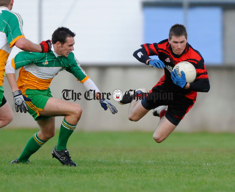Clondegad's Brian Murphy goes flying as Kildysart-Colmeen's Alan Markham moves in during their U-21 b county football final at Cooraclare. Photograph by John Kelly.