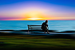 Conceptual beach scene with figure seated on bench resting head on hand