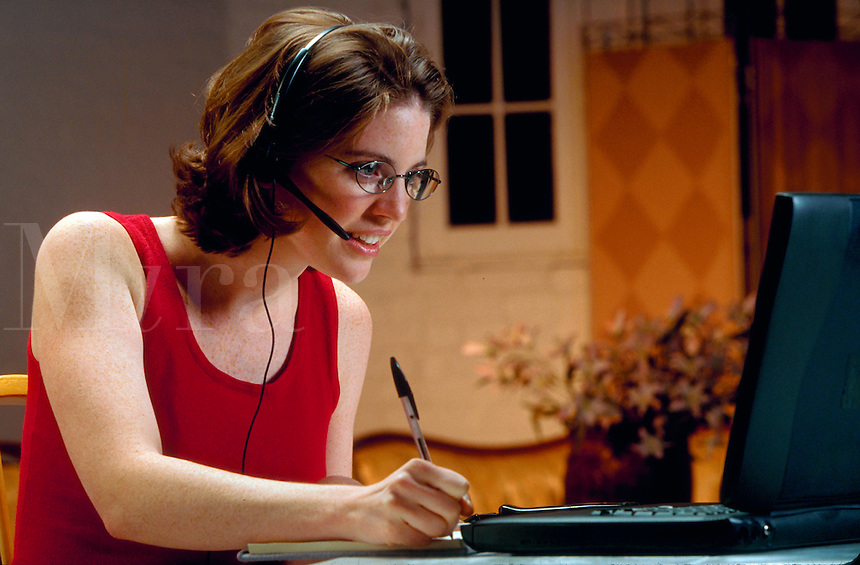 A smiling young woman in glasses talking on a telephone headset and working with a laptop computer.