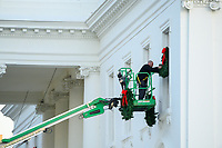 A worker hangs Christmas wreaths on the White House windows in Washington, DC on Monday, November 25, 2019. <br /> Credit: Erin Scott / CNP/AdMedia