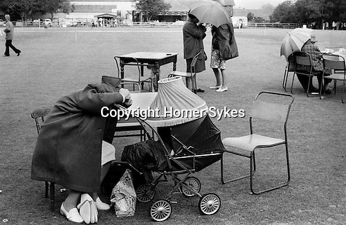 Cirencester, Gloucestershire. 1974<br /> The Church of St. John the Baptist annual summer fete, women shelter from the rain.