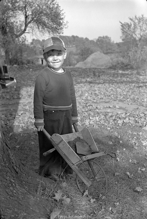 A young boy poses with his toy wheelbarrow. Circa 1920.