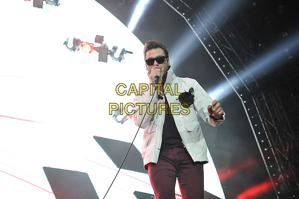 Tom Meighan.Kasabian performing live in concert, O2 Arena, Greenwich, London, England. 14th December 2011.on stage gig performance music half length white jacket purple jeans denim sunglasses shades corsage microphone singing .CAP/MAR.© Martin Harris/Capital Pictures.