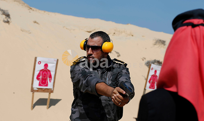 A Palestinian woman fires at a target during a training session for the families of Hamas officials, organized by Hamas-run Security and Protection Service, in Khan Younis in the southern Gaza Strip July 24, 2016. Photo by Ramadan El-agha