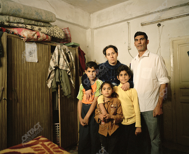 Fatin 30, wife of Samir 44, with three of their four children in the bedroom of their two room apartment in the Hashmi Al Shemali area of Amman.  They are living as refugees in Amman with a total of 19 family members. Samir did some work for the British during the war and received death threats. Other family members have also been affected by persecution, rape, gun shot wounds, and other types of physical abuse. They are Sabian Mandaean, a minority group in Iraq who have suffered extreme cases of persecution. Hashmi Al Shemali area of Amman, Jordan, April, 2007