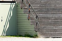 Shadows from a bannister on a big wooden outdoor staircase, showing on an green painted iron door, at the Beach by the Sea in Ebeltoft, Denmark Scandinavia.