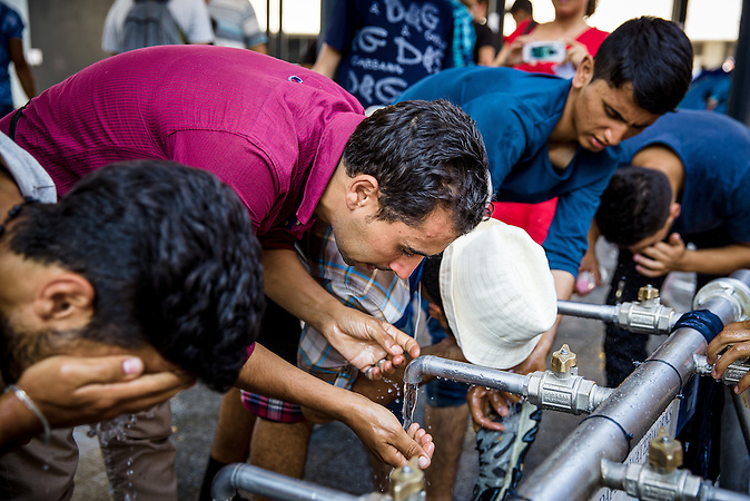 Peolple drink and wash their faces and feet at the sinks set up at Keleti Railway Station// Situation nach der Räumung der Flüchtlinge  am Keleti Bahnhof in Budapest //  Situation at the Keleti Railwaystation in Budapest Hungary 01.09.2015