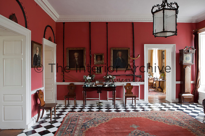 The red-painted entrance hall has a black and white marble floor and is furnished with a set of Irish Georgian hall chairs