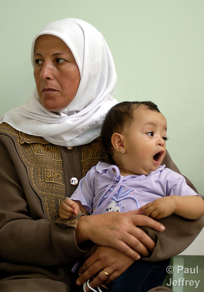 A woman and her child wait to be seen in the health center in the Ama'ri Refugee Camp in Ramallah.