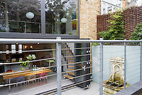 Folding glass doors from the kitchen/dining area open onto a sunken courtyard which features an antique marble fountain