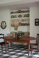 One end of the kitchen is occupied by a small dining area decorated with a collection of assorted porcelain plates