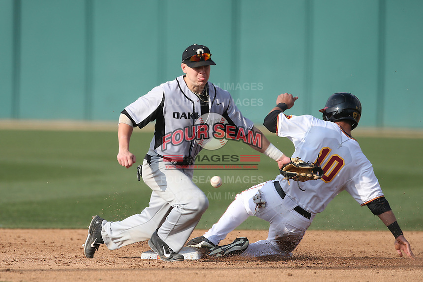 Mike Brousseau (10) of the Oakland Grizzlies can't handle the throw as A.J. Ramirez of the Southern California Trojans slides into second base during a game at Dedeaux Field on February 21, 2015 in Los Angeles, California. Southern California defeated Oakland, 11-1. (Larry Goren/Four Seam Images)