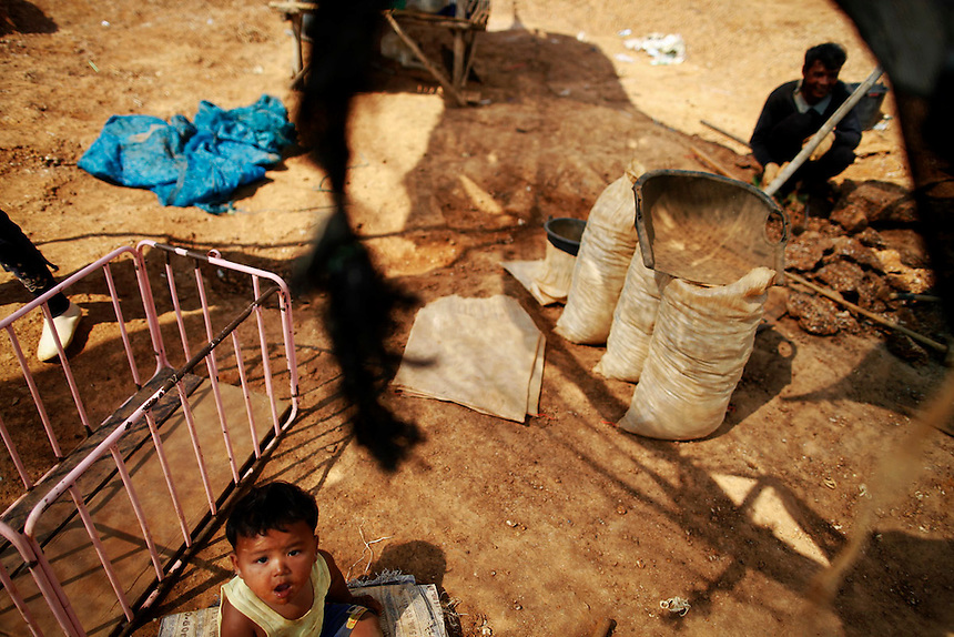 A child sits under netting as people work at a primitive gold mine in Panompa near Phichin February 17, 2011. A group of Thais use primitive tools and methods to extract gold from self-run mines near the countries biggest and most modern Chatree gold mine. A family working at the mine can get around one gram of gold per day they sell at the site for about 1000 Thai bahts (32 USD).   REUTERS/Damir Sagolj (THAILAND)