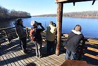 Visitors look at birds in February 2020 from a wildlife viewing pavilion at the Eagle Watch Nature Trail. The trail and lake are a popular with birders and hikers. Bird species should increase now that spring migration has started for all kinds of birds.<br />