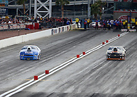 Mar 29, 2014; Las Vegas, NV, USA; NHRA pro stock driver Larry Morgan (left) races alongside Steve Kent during qualifying for the Summitracing.com Nationals at The Strip at Las Vegas Motor Speedway. Mandatory Credit: Mark J. Rebilas-