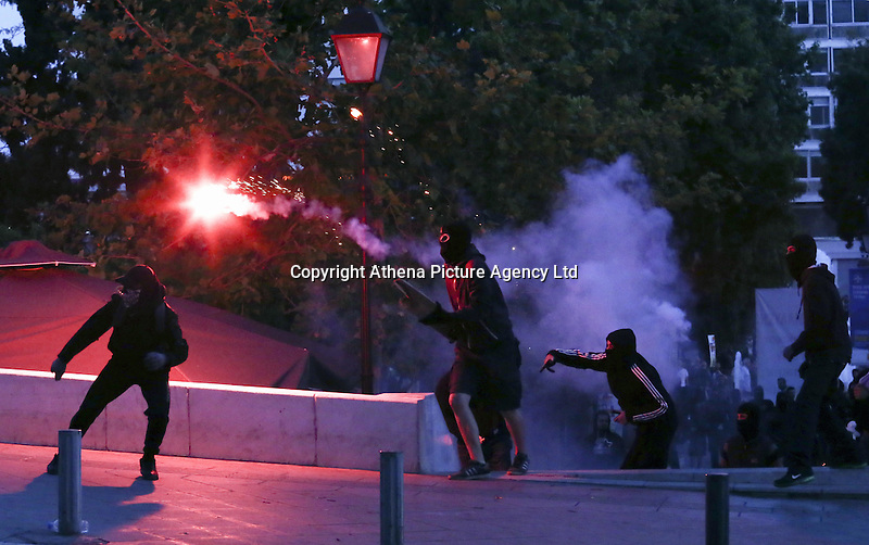 Pictured: A protester throws a flare Sunday 09 May 2016<br />