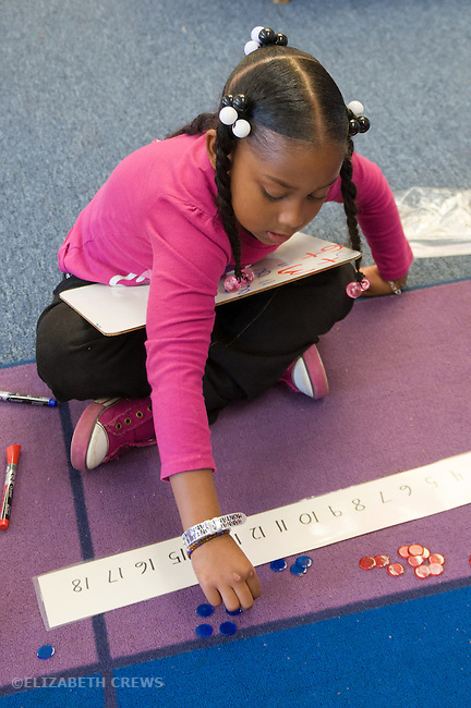 Berkeley CA Kindergarten student,African American, working on addition with math manipulatives