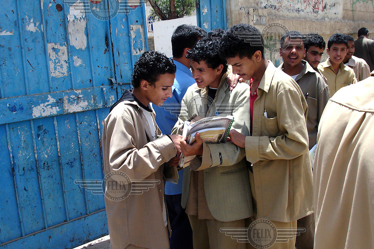 Students discuss schoolwork outside a school in Sana'a.