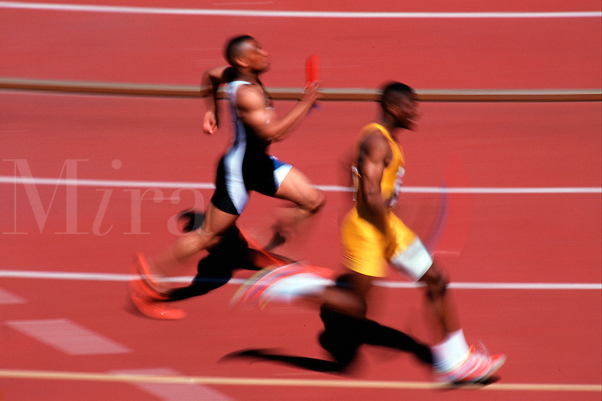Blurred action image of a male runners at a track meet.