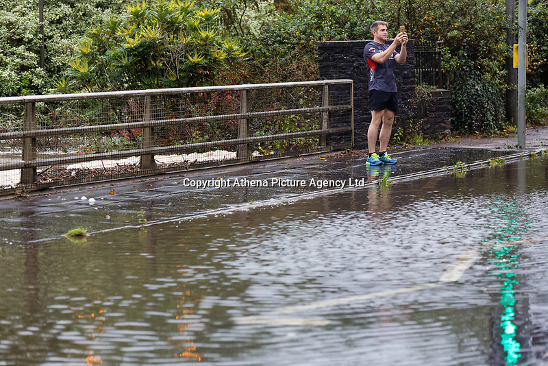 Pictured: A jogger pauses to take a picture of the flooded A4119 outside Aberdulais Falls in south Wales, UK. Saturday 13 October 2018<br /> Re: Flooding caused by Storm Callum in Aberdulais near Neath, south Wales, UK.
