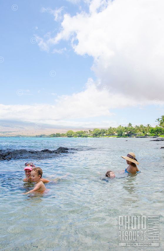 Two local families swim in and explore the tide pools at a beach in Puako, South Kohala, Hawai'i Island