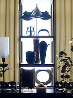 A variety of objects is displayed on open shelving silhouetted against the windows of the living room