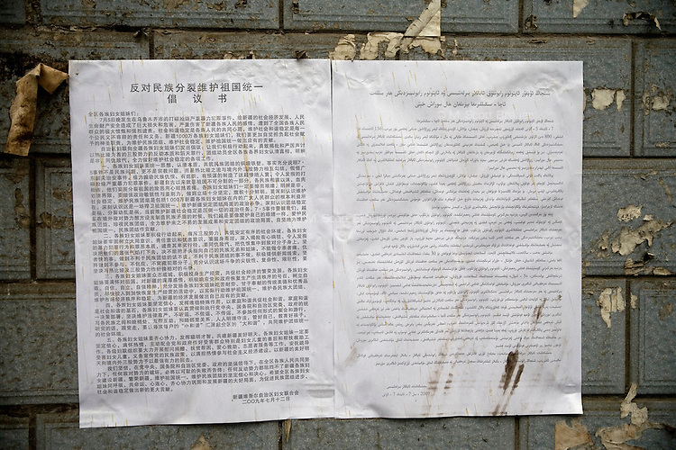 A public notice regarding ethnic violence hangs on a wall in a Han neighborhood in Urumqi, Xinjiang, China.  The sign is in Mandarin and Uighur language. The city is divided between Han and Uighur ethnicities, and violent clashes erupted between the groups in 2009.