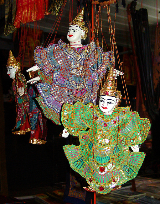 Two marionettes hanging by their strings in a Thai marketplace. One marionette is primarily in blues and reds and the other is in bright greens outline in red. Both have the traditional headwear, white gloved hands and pointed shoes.