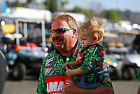 Feb 8, 2015; Pomona, CA, USA; Terry McMillen holds son Cam McMillen during the Winternationals at Auto Club Raceway at Pomona. Mandatory Credit: Mark J. Rebilas-