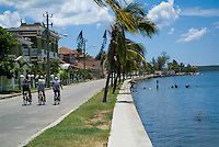 Men cycling along the street together by Cienfuegos Bay, Punta Gorda, Cuba.
