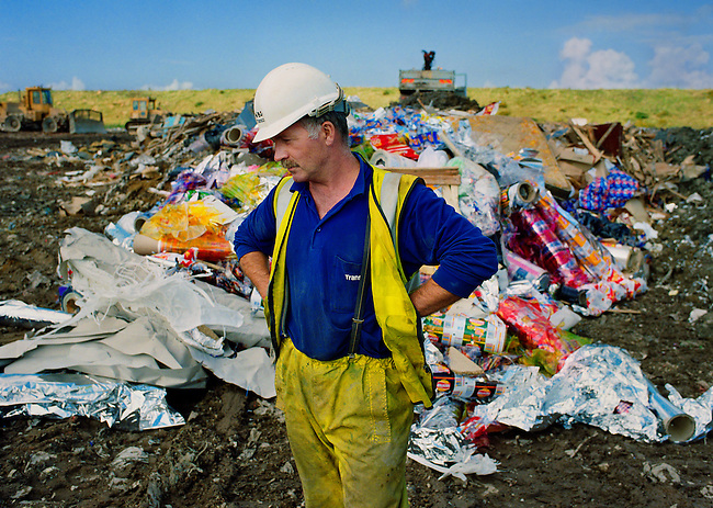 Worker surrounded by unused Walkers crisp packaging at a landfill site.
