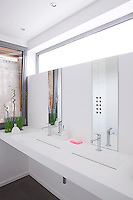A pair of shallow wash basins is complemented by matching mirrors on a minimal washstand which has been placed across a picture window