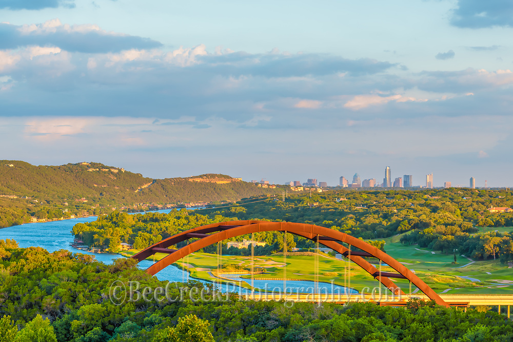 Another photo of Austin Pennybacker Bridge.  It hard to get enough photo of this bridge. The Pennybacker Bridge with Lake Austin flowing underneath it a very scenic location to photograph.   This day we had some interesting clouds and the austin city skyline in the background as the sun was getting lower in the sky The Austin 360 bridge is an iconic view of austin with the scenic blue waters of the lake meandering toward the city with all the greenery from the golf corse and trees with the Austin cityscape.
