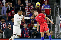 ORLANDO, FL - NOVEMBER 15: Jordan Morris #13 of the United States and Derek Cornelius #4 of Canada battle in the air for a ball during a game between Canada and USMNT at Exploria Stadium on November 15, 2019 in Orlando, Florida.