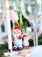 Two peculiar gnomes stand among sprigs of juniper along the Christmas dining table