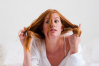 Young red haired woman playing with her hair