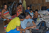 Mato Grosso State, Brazil. Aldeia Metuktire (Kayapo). Patrick Cunningham working on the MacBook laptop with an audience.