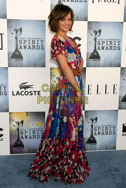 MENA SUVARI.2009 Film Independent Spirit Awards held at the Santa Monica Pier, Santa Monica, California, USA..February 21st, 2009.full length blue pink red multi coloured floral print gold maxi dress long waist belt brown pattern.CAP/ADM/MJ.©Michael Jade/AdMedia/Capital Pictures.