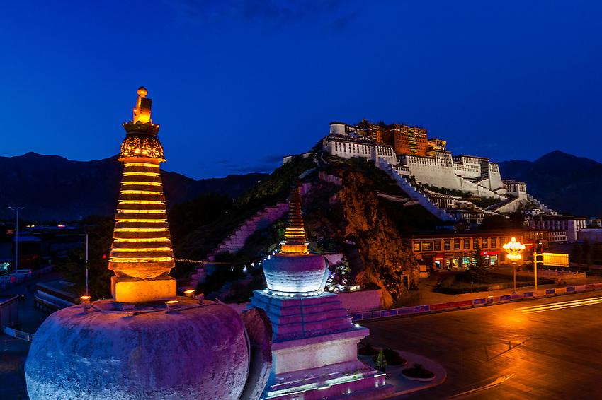 The Potala Palace with stupas in the foreground illuminated at twilight, Lhasa, Tibet (Xizang), China.