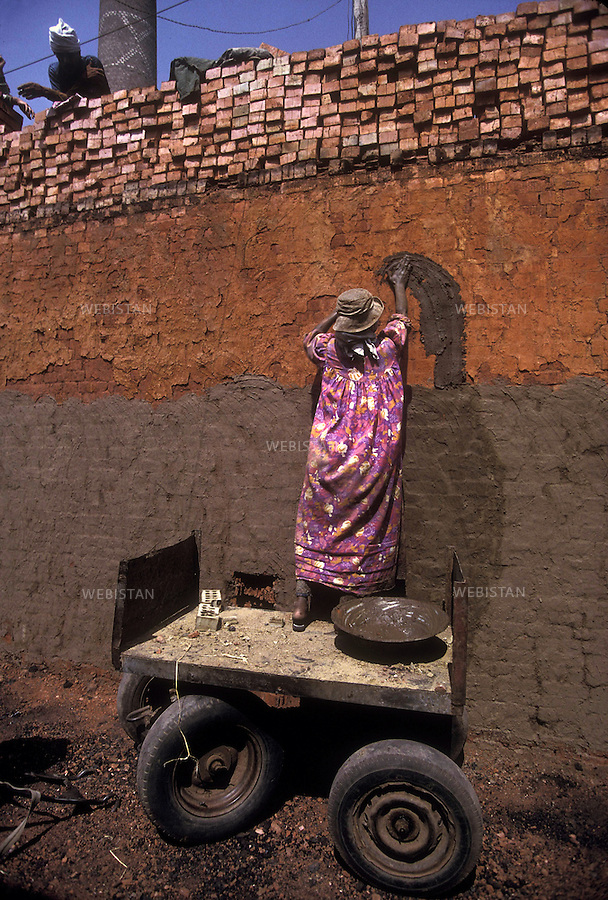 Egypt. Tabakh's brickyard. May 1996. In Tabakh's brickyard, near Zifta, a woman coats a wall with her hand..Egypte. Tabakh, pres de Zifta. Mai 1996. Dans la briqueterie de Tabakh, une ouvriere enduit un mur a la main..