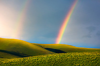 A beautiful double rainbow forms over the layered Columbia HIlls in the late afternoon on the edge of a weather front.<br />