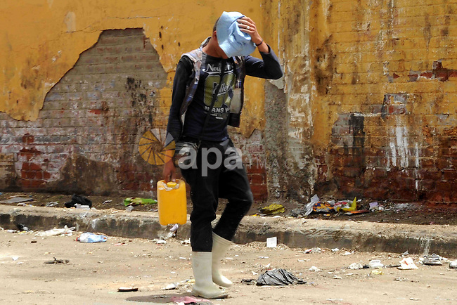 An Egyptian man carries a water bottle as he walks in a street in downtown Cairo on May 27, 2015. Hot weather with sandstorm hit Egypt on Wednesday, and the temperature reached 44 degree Celsius (111 degree Fahrenheit) at noon in some regions of the country. Photo by Amr Sayed